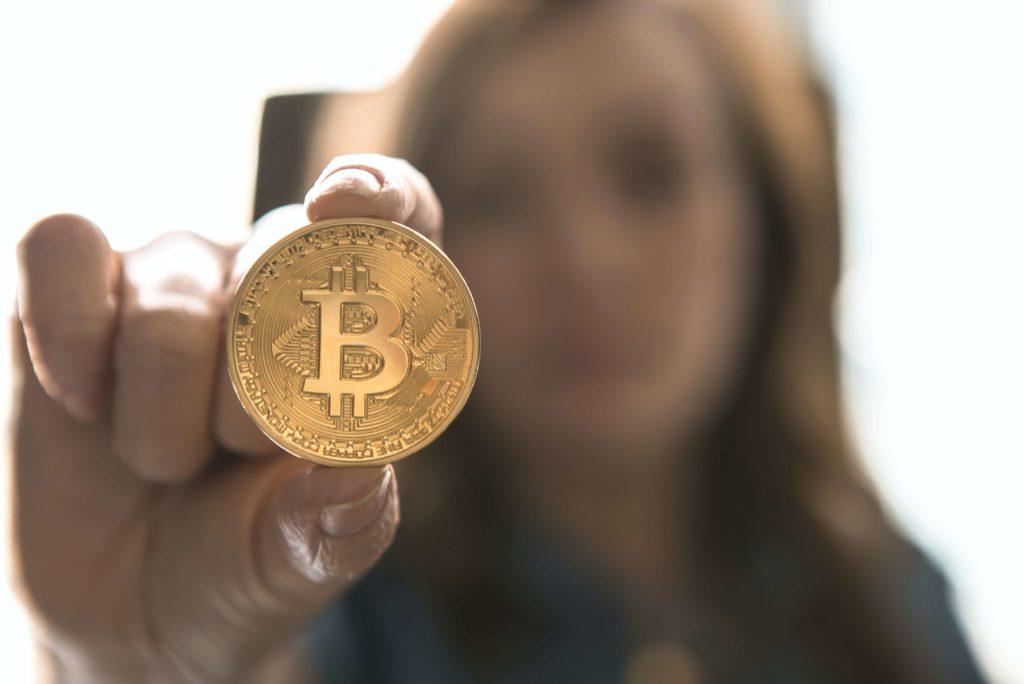 Frau hält Bitcoin Münz-Modell in die Kamera
